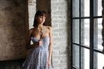 Обои Симпатичная темноволосая девушка в приспущенном с плеч платье позирует, стоя у окна в комнате. Фотограф Gene Oryx