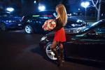 Обои Девушка с букетом в руках стоит возле автомобиля