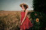 Обои Симпатичная девушка в шляпке и в платье в горошек позирует, стоя на краю поля на фоне природы