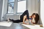 Обои Спортивная девушка занимается йогой на полу у окна