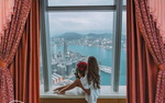 Обои Девушка с букетом красных роз сидит на подоконнике и смотрит на город