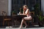 Обои Симпатичная девушка в розовом платье сидит за столиком с кружкой напитка, на фоне окна здания и растений. Фотограф Олег Климин