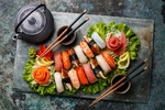 Обои Японская кухня: ассорти из суши с красной рыбой на листьях салата, рядом соус, маринованный имбирь, васаби и палочки для еды