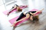 Обои Две спортивные девушки занимается йогой на коврике в светлом зале