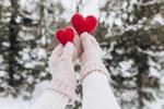 Обои Две руки в варежках держат сшитые сердечки