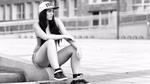 Обои Девушка со скейтбордом сидит на бордюре