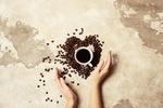 Обои Кофейные зерна в форме сердца и чашка с кофе на фоне ткани перед руками девушки, by Alla Simacheva