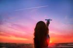 Обои Девушка держит модель самолета в руке на фоне неба во время захода солнца, by Alla Simacheva