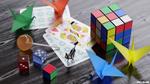 Обои Кубик Рубика, игральные кости, карты, бумажные журавлики, чупа-чупс и фигурка кошки на столе, by mclelun