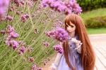 Обои Кукла с длинными волосами стоит у цветов
