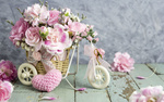 Обои Розовые гвоздики на игрушечном велосипеде, розовое вязанное сердечко на столе