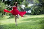 Обои Азиатка в красном коктейльном платье танцует босиком на зеленой лужайке в парке