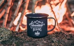 Обои Чашка с надписью The adventure begins / Приключения начинаются стоит на фоне костра