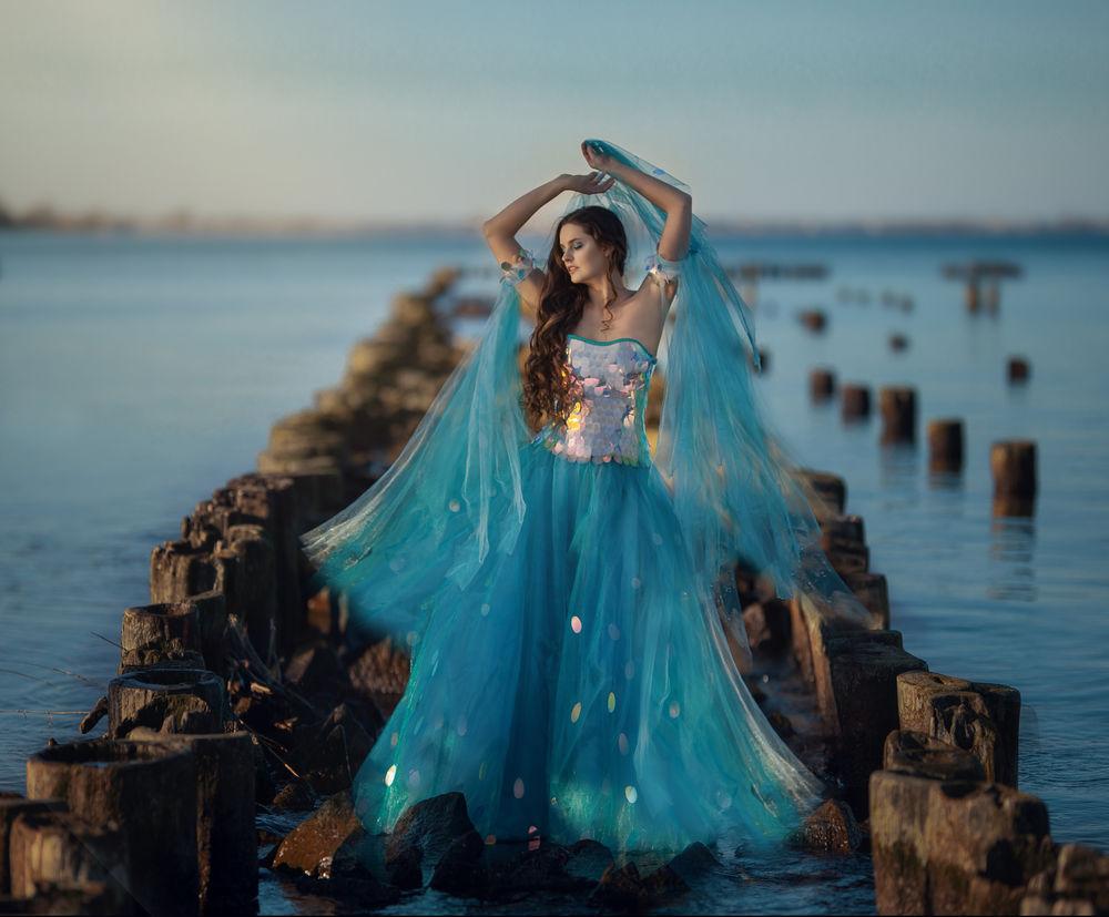 Обои для рабочего стола Модель Karolina Ciеszka в голубом платье стоит среди деревянных столбов в воде, фотограф Ragan Sylwia
