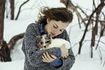 Обои Девушка со щенком на руках стоит на фоне заснеженной природы, фотограф Lara Wernet