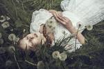 Обои Модель Thinloth с отцветшими одуванчиками в руках лежит на траве. фотограф Dorota Gorecka