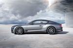 Обои Серебристый Bentley Continental / Бентли Континенталь стоит у круглово здания под облачным небом