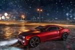 Обои Красный Chevrolet Camaro стоит ночью на городской площадке под падающим снегом на фоне зажженных фонарных столбов, фотограф doberman