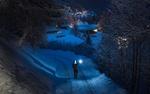 Обои Мужчина с фонариком идет по заснеженной дороге в сторону домов