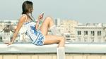 Обои Девушка с телефоном сидит на крыше
