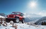 Обои Красный Jeep Rubicon в заснеженных горах солнечным днем