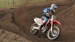 Обои Гонщик мотокросса поднимает куски грязи колесом своего мотоцикла в стремительном повороте