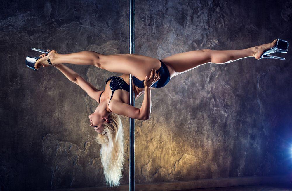 Обои для рабочего стола Блондинка в темном купальнике исполняет танец на пилоне
