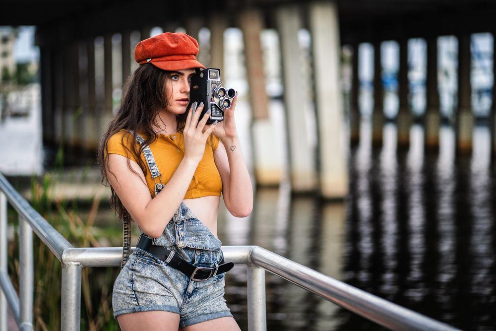 Обои для рабочего стола Темноволосая девушка в кепи, приспущенном джинсовом комбинезоне с кинокамерой в руках стоит у ограждения, на размытом фоне водоема, фотограф Christopher Rankin