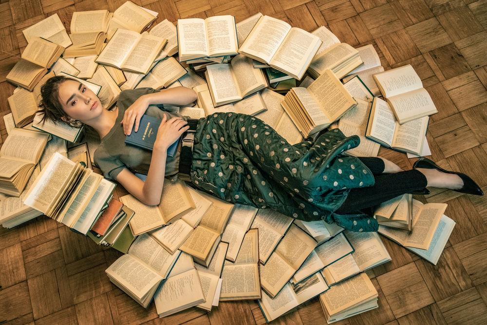 Обои для рабочего стола Модель Анна Пагута с книгой в руке лежит на полу в окружении книг, by Ilya Blinov