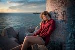 Обои Девушка в красной рубашке сидит у бетонной колонны на фоне моря