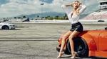 Обои Модель Lauren York в белой рубашке и в кожаной юбке сидит на на авто на поле автодрома