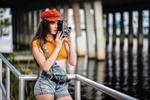 Обои Темноволосая девушка в кепи, приспущенном джинсовом комбинезоне с кинокамерой в руках стоит у ограждения, на размытом фоне водоема, фотограф Christopher Rankin