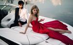 Обои Девушка в красном платье с бокалом в руке сидит на катере перед парнем