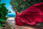 Обои Девушка в длинном красном платье стоит у цветущего дерева. Фотограф Илья Ткачев