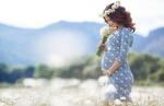 Обои Беременная женщина с ромашками на фоне гор