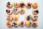 Обои Много пирожных с красиво украшенных свежими ягодами и фруктами, живыми цветами, вид сверху