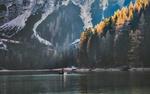 Обои Люди в лодке плывут по спокойной воде озера, расположенного у гор и леса