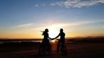 Обои Парень с девушкой на велосипедах стоят на фоне заката солнца