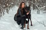 Обои Девушка с длинными волосами в кожаной куртке и в черных джинсах обнимает собаку породы доберман, сидя на коточках на фоне зимнего парка, фотограф Дмитрий Шульгин