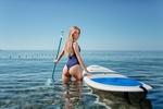 Обои Блондинка с длинными волосами в купальном костюме стоит в водоеме, держась рукой за доску для серфинга, фотограф Евгений Фрейер