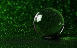 Обои Стеклянный шар на зеленой поверхности