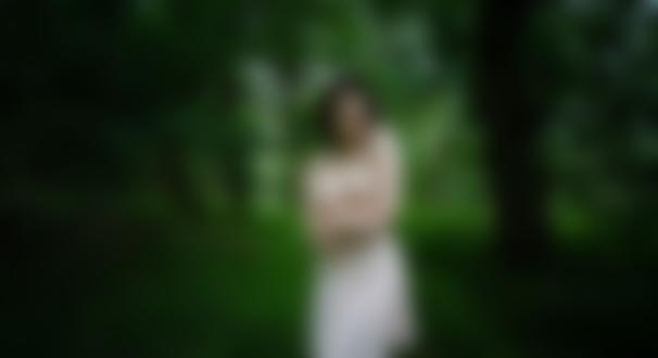 Обои Брюнетка в приспущенном светлом платье топлес позирует, стоя в лесу