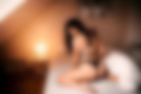 Обои Брюнетка в черном нижнем белье стоит спиной к камере на коленях на кровати в спальной комнате