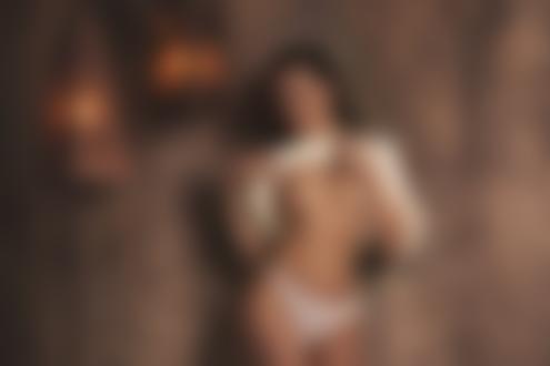 Обои Темноволосая девушка в приподнятой белой кофте и в белых трусиках стоит у стены в помещении