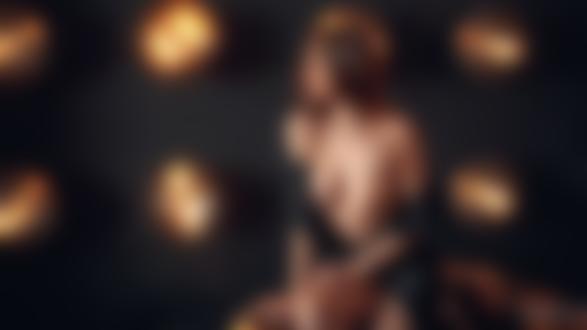Обои Модель Женя в расстегнутом черном платье сидит на кресле в помещении, на фоне стены с подсветкой, фотограф Антон Артюшин