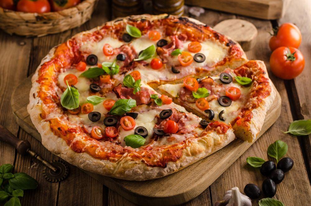 Обои Аппетитная пицца на деревянной доске, рядом оливки, чеснок и листья  шпината на рабочий стол
