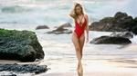 Обои Модель Tiffany Toth в красном купальнике стоит на каменистом морском берегу