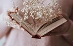 Обои В руках девушки открытая книга м белыми цветочками