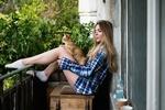 Обои Девушка в клечатой рубашке с кошкой на коленях сидит на баконе здания, положив ноги на ограждение
