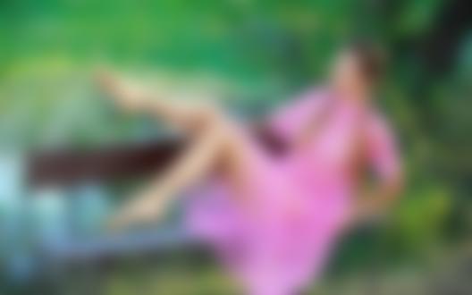 Обои для рабочего стола Девушка с косичками в прозрачном розовом платье лежит на скамейке у водоема на фоне природы
